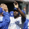 Kansas City Royals\' Lorenzo Cain is congratulated after scoring during the fourth inning of a baseball game against the Detroit Tigers in Detroit, Monday, March 31, 2014. (AP Photo/Carlos Osorio)
