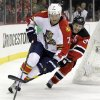 Photo -   Florida Panthers' Dmitry Kulikov, left, of Russia, and New Jersey Devils' Zach Parise compete for the puck during the second period of Game 3 of a first-round NHL hockey Stanley Cup playoff series, Tuesday, April 17, 2012, in Newark, N.J. (AP Photo/Julio Cortez)