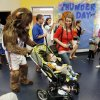 Oklahoma City Thunder mascot Rumble pushes Kannon Foster, 2, in a stroller Thursday while his mother, Kelli, watches at a