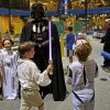 Photo - Dressed as Darth Vader, Shawn Lippe, of Oklahoma City, attracts a crowd of children during  Science Museum Oklahoma's Bright Night of Star Wars sleepover. Photo by Bryan Terry, The Oklahoman  Bryan Terry - THE OKLAHOMAN