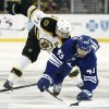 Toronto Maple Leafs\' Nazem Kadri (43) reaches for the puck past Boston Bruins\' Patrice Bergeron during the first period of an NHL hockey game in Boston on Monday, March 25, 2013. (AP Photo/Winslow Townson)