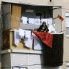 A woman is fixing an Albanian flag with the laundry on a balcony in Skopje, Macedonia, on Saturday, Nov.24, 2012. Macedonian capital Skopje, particularly the parts populated with ethnic Albanians, are flooded with Albanian flags, in the eve of the celebration of 100 years of Albania\'s independence and the national flag. Ethnic Albanians make up a quarter of Macedonia\'s 2.1 million people and are the largest ethnic minority in the country. (AP Photo/Boris Grdanoski)