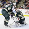 Photo - Minnesota Wild goalie Niklas Backstrom, right, of Finland, deflects a shot by Washington Capitals right wing Eric Fehr, center, as Wild defenseman Jonas Brodin (25) defends during the second period of an NHL hockey game in St. Paul, Minn., Saturday, Jan. 4, 2014.   (AP Photo/Ann Heisenfelt)