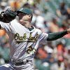 Photo - Oakland Athletics starting pitcher Scott Kazmir throws against the San Francisco Giants in the first inning of their interleague baseball game Thursday, July 10, 2014, in San Francisco. (AP Photo/Eric Risberg)