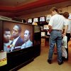 """Photo - FILE - In this June 20, 1994 file photo, mall shoppers in Tampa, Fla., watch banks of televisions in an electronics store as the arraignment of O.J. Simpson is televised from Los Angeles. The O.J. Simpson trial was labeled the """"Trial of the century"""" and a forerunner of today's interactive media. (AP Photo/Chris O'Meara, File)"""