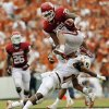 Oklahoma\'s Trey Millard jumps over Texas defender Adrian Phillips during last year\'s 63-21 win. PHOTO BY NATE BILLINGS, THE OKLAHOMAN