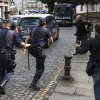 Photo - Media run after a police car carrying arrested train driver Francisco Jose Garzon Amo, unseen, to testify in court in Santiago de Compostela, Spain, Sunday, July 28, 2013. The driver of a Spanish train that derailed at high speed was being questioned by a judge on Sunday as officials tried to determine if he was responsible for the accident, which killed 79 people. Francisco Jose Garzon Amo, 52, has been held by police on suspicion of reckless homicide. (AP Photo/Lalo R. Villar)