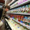 Photo - In this May 23, 2014 photo, grocery and dairy assistant Reyna DeLoge stocks dairy products that only use milk from pasture-raised cows, at Vitamin Cottage Natural Grocers, in Denver. The Colorado-based grocery store chain recently announced that it will carry only dairy products from farms where cows graze on pasture, talking the position that grazing improves the health of cows and consumers. (AP Photo/Brennan Linsley)