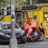 Photo - Honolulu firefighters look over the wreckage of a small helicopter that crashed next to a car near the intersection of Fort Street and Beretania Street in downtown Honolulu Wednesday, May 8, 2013. (AP Photo/Eugene Tanner)