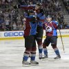 Photo - Colorado Avalanche center Nathan MacKinnon (29) jumps on Nate Guenin (5) as Tyson Barrie (4) cheers following Guenin's goal against the Phoenix Coyotes while during the third period of an NHL hockey game on Friday, Feb. 28, 2014, in Denver. (AP Photo/Jack Dempsey)
