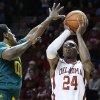 Oklahoma guard Buddy Hield (24) fakes a shot before passing to a teammate in front of Baylor forward Royce O\'Neale (00) in the second half of an NCAA college basketball game in Norman, Okla., Saturday, Feb. 8, 2014. Oklahoma won 88-72. (AP Photo/Sue Ogrocki)