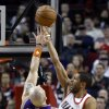 Portland Trail Blazers forward Nicolas Batum, right, from France, shoots over Phoenix Suns center Marcin Gortat, from Poland, during the first quarter of an NBA basketball game in Portland, Ore., Saturday, Dec. 22, 2012. (AP Photo/Don Ryan)