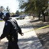 A Phoenix Police Department officer, puts up police tape near a home of a suspected gunman who opened fire at a Phoenix office building on, wounding three people, one of them critically, and setting off a manhunt that led police to surround his house for several hours before they discovered he wasn\'t there, Wednesday, Jan. 30, 2013, in Phoenix. Authorities believe there was only one shooter, but have not identified him or a possible motive for the shooting. They don\'t believe the midmorning shooting at the complex was a random act. (AP Photo/Ross D. Franklin)