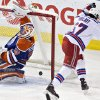 New York Rangers Benoit Pouliot (67) celebrates as the puck goes past Edmonton Oilers Ben Scrivens (30) during second period NHL hockey action in Edmonton, Alberta, on Sunday March 30, 2014. (AP Photo/The Canadian Press, Jason Franson)