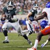Photo -   FILE - In this Aug. 31, 2012, file photo, Michigan State's Le'Veon Bell (24) gets past Boise State's Jerell Gavins (5) to score the game-winning touchdown during the fourth quarter of an NCAA college football game in East Lansing, Mich. Bell figured to have a bigger role this season in Michigan State's backfield, but his opening game last week against Boise State was a head turner. Bell had 44 carries for 210 yards in perhaps the best offensive performance by any player in the country.(AP Photo/Al Goldis, File)