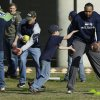 Seattle Seahawks linebacker K.J. Wright, right, and Bryan Walters, third from right, hand off footballs to kids Monday, March 31, 2014, at a community gathering in Darrington, Wash. The NFL football players and other team officials visited Darrington to lend support to the town, which is located near the site of the deadly mudslide that hit the community of Oso,Wash. on March 22, 2014. (AP Photo/Ted S. Warren)