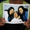 A man holds a print of one of the photographs released Friday by the government showing President Hugo Chavez with his daughters Maria Gabriela, left, and Rosa Virginia, right, at Bolivar square in Caracas, Venezuela, Friday, Feb. 15, 2013. Amid widespread speculation and rumors in Venezuela about Chavez\'s delicate condition following his Dec. 11 cancer surgery, the government released the first photos of the ailing president in more than two months on Friday, presenting images of him smiling alongside his daughters in Cuba. (AP Photo/Fernando Llano)
