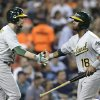 Photo - Oakland Athletics second baseman Alberto Callaspo (18) is congratulated by Jed Lowrie (8) after scoring on a Coco Crisp single against the Detroit Tigers in the sixth inning of a baseball game in Detroit, Monday, Aug. 26, 2013. (AP Photo/Paul Sancya)
