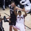 Photo - Toronto Raptors guard Kyle Lowry (7) loses control of the ball while driving toward the net past Brooklyn Nets' Mirza Teletovic, center, and Deron Williams, left, during the second half of Game 5 of the opening-round NBA basketball playoff series in Toronto, Wednesday, April 30, 2014. (AP Photo/The Canadian Press, Nathan Denette)