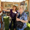 Photo - Artist Kathy Morrow shows her work to Louise Lazalier at the annual May Fair Festival Saturday at Andrews Park in Norman. PHOTO BY STEVE SISNEY, THE OKLAHOMAN <strong>STEVE SISNEY</strong>