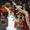 Oklahoma State\'s Keiton Page (12) passes the ball past Oklahoma\'s Cade Davis (34) in the first half of the college basketball game during the men\'s Big 12 Championship tournament at the Sprint Center on Wednesday, March 10, 2010, in Kansas City, Mo. Photo by Chris Landsberger, The Oklahoman