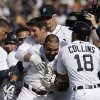 Detroit Tigers\' Alex Gonzalez, center, is mobbed after hitting the game winning single to score the winning run from third during the ninth inning of a baseball game against the Kansas City Royals in Detroit, Monday, March 31, 2014. (AP Photo/Carlos Osorio)