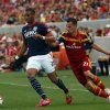 Photo - New England Revolution defender Darrius Barnes (25) dribbles the ball as Real Salt Lake midfielder Luis Gil (21) puts pressure on in the first half of an MLS soccer match on Friday, July 4, 2014, in Sandy, Utah. (AP Photo/Kim Raff)
