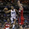 Charlotte Bobcats\' Ramon Sessions, center, drives between Washington Wizards\' Marcin Gortat, right, and Martell Webster (9) during the first half of an NBA basketball game in Charlotte, N.C., Tuesday, Jan. 7, 2014. (AP Photo/Chuck Burton)