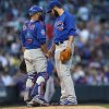 Photo - Chicago Cubs catcher Wellington Castillo, left, confers with starting pitcher Jake Arrieta after Arrieta gave up an RBI single to Colorado Rockies' Michael McKenry in the fourth inning of the Rockies' 13-4 victory in a baseball game in Denver on Wednesday, Aug. 6, 2014. (AP Photo/David Zalubowski)