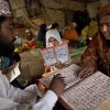 Photo - Pakistani woman Halimah Tajj, 51, right, repeats after her teacher Mohammad Shiraz, 24, left, during a three hour daily class for illiterate women and children on how to read Urdu alphabet and verses of the holy Quran, in a makeshift tent on the outskirts of Islamabad, Pakistan, Tuesday, April 2, 2013. According to the United Nations, only 40 percent of Pakistani girls 15 or younger are literate in Pakistan. (AP Photo/Muhammed Muheisen)