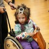 Mina Millet, a kindergarten student at Epperly Heights Elementary School, attends the party in her wheelchair. Midwest City parks and recreation department hosted a trick or treat Halloween party for special needs children in the Nick Harroz Community Center Thursday afternoon, Oct. 31, 2013. A parks spokesperson said about 150 children, wearing costumes, attended the event. The children are students at local elementary schools. Students from Carl Albert Middle School Key Club volunteered at the carnival booths and they handed out candy and treats to the children as they entered the building. Photo by Jim Beckel, The Oklahoman.
