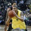 Photo - Oregon's Joseph Young dive ahead of Southern California's J. T. Terrell as he passes to a teammate during the first half of an NCAA college basketball game in Eugene, Ore. on Saturday, Feb. 1, 2014. (AP Photo/Chris Pietsch)