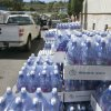 Cases of water are seen curbside at the Menehune Water Company, Aug. 7, 2014, in Aiea, Hawaii. Hawaii is bracing for two back to back hurricanes, Iselle and Julio, which are on course to hit the Islands. Bottles of water are quickly disappearing off shelves in Hawaii causing many people to line up for several hours to purchase water directly from the company. (AP Photo/Marco Garcia)