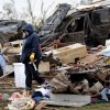 Dena Gower carries a cross from her destroyed home on Tuesday, May 21, 2013 in Moore, Okla. to put in the yard of her neighbor who was killed by Monday\'s tornado in the area near 4th and Bryant. Photo by Chris Landsberger, The Oklahoman