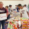 Photo - Jacob Jorday, 16, (left) and Jimmie Grizzard, 15, move down the line as Edmond football players pack care packages to send to deployed military during a Blue Star Mother's event at the Peace Lutheran Church in Edmond, OK, Saturday, July 24, 2010. By Paul Hellstern, The Oklahoman
