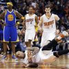 Phoenix Suns\' P.J. Tucker, front, falls to the court after sinking a jump shot while being fouled by Golden State Warriors\' Jermaine O\'Neal (7) as Suns\' Goran Dragic (1), of Slovenia, and Channing Frye (8) run over to Tucker during the first half of an NBA basketball game Saturday, Feb. 8, 2014, in Phoenix. (AP Photo/Ross D. Franklin)
