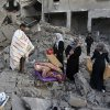 Palestinians collect their belongings from the rubble of the building of Attia Abu Inkara, a Hamas militant leader, following an Israeli air strike in Rafah refugee camp in southern Gaza Strip, Sunday, Nov. 18, 2012. An Israeli envoy held talks with Egyptian officials Sunday on a ceasefire in his country\'s offensive on Gaza as Israel widened the range of its targets, striking more than a dozen homes of Hamas militants and two media officials. (AP Photo/Eyad Baba)
