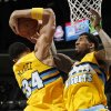Denver Nuggets forwards JaVale McGee, left, and Wilson Chandler get tied up with each other on a rebound, against the Boston Celtics in the first quarter of an NBA basketball game in Denver on Tuesday, Feb. 19, 2013. (AP Photo/David Zalubowski)