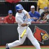 Photo - Kentucky's Max Kuhn hits a single up the middle during an NCAA college baseball regional tournament game against Kansas in Louisville, Ky., Friday, May 30, 2014. (AP Photo/Timothy D. Easley)