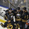 Photo - Buffalo Sabres' Alexander Sulzer (52) celebrates with teammates Christian Ehrhoff (10), Matt D'Agostini (27) and Steve Ott (9) after D'Agostini scored the game-winning goal in the overtime session against the  Boston Bruins during an NHL hockey game in Buffalo, N.Y., Wednesday, Feb. 26,  2014. Buffalo won 5-4. (AP Photo/Gary Wiepert)