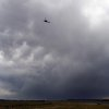 A helicopter flies underneath a thunderstorm that dumped rain on a trouble area of the Black Forest Fire near Colorado Springs, Colo. on Friday, June 13, 2013. Authorities lifted evacuations in a wide swath of terrain outside Colorado Springs on Friday as they said a surprise rain shower helped them expand containment of a wildfire that has destroyed 400 homes. (AP Photo/Bryan Oller)