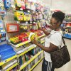 Photo -  Andrea Greene, of Moore, looks at a school supply checklist in August while shopping for her two children on the school supply aisle at Dollar General in Moore. Photo by Paul B. Southerland, The Oklahoman Archives   PAUL B. SOUTHERLAND -  PAUL B. SOUTHERLAND