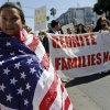 Maria Fernanda Medina, 7, wraps herself in a United States flag as she marches with her father, Jorge, during a May Day demonstration in San Francisco, Wednesday, May 1, 2013. Demonstrators demanded an overhaul of immigration laws Wednesday in an annual, nationwide ritual that carried a special sense of urgency as Congress considers sweeping legislation that would bring many of the estimated 11 million people living in the U.S. illegally out of the shadows. (AP Photo/Marcio Jose Sanchez)