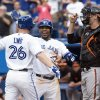 Toronto Blue Jays\' Adam Lind, left, celebrates with Edwin Encarnacion after hitting a two-run homer off Baltimore Orioles starting pitcher Jason Hammel as Orioles catcher Matt Wieters looks on during the first inning of a baseball game in Toronto on Friday, June 21, 2013. (AP Photo/The Canadian Press, Chris Young)