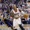 Photo - Portland Trail Blazers guard Damian Lillard, right, drives past New Orleans Pelicans guard Jrue Holiday during the first half of an NBA basketball game in Portland, Ore., Saturday, Dec. 21, 2013. (AP Photo/Don Ryan)