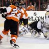 Photo - Philadelphia Flyers' Mattt Read, left, scores against a diving Pittsburgh Penguins goalie Marc-Andre Fleury during the second period of an NHL hockey game, Saturday, March 15, 2014, in Philadelphia. (AP Photo/Tom Mihalek)