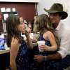 Photo -  The Red Dirt Rangers' Brad Piccolo eats ice cream Friday with his daughters Isabel, 9, right, and Ruby, 7, at Sooner Drug Store & Gifts during the Woody Guthrie Festival in Okemah.   SARAH PHIPPS