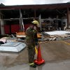A firefighter talks on a cell phone in front of damage to the Chuck E Cheese restaurant following storms near NW Expressway and Rockwell in Oklahoma City on Tuesday, Feb. 10, 2009. By John Clanton, The Oklahoman