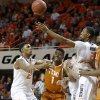 Texas\' Isaiah Taylor (1) passes the ball from between Oklahoma State\'s Le\'Bryan Nash (2), Phil Forte (13) and Kamari Murphy (21) during an NCAA college basketball game between the Oklahoma State Cowboys (OSU) and the University of Texas Longhorns at Gallagher-Iba Arena in Stillwater, Okla., Wednesday, Jan. 8, 2014. Photo by Bryan Terry, The Oklahoman