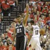Photo - San Antonio Spurs' Tim Duncan (21) points after fouling as Portland Trail Blazers' LaMarcus Aldridge (12) walks on in the first quarter during Game 4 of a Western Conference semifinal NBA basketball playoff series Monday, May 12, 2014, in Portland, Ore. (AP Photo/Rick Bowmer)